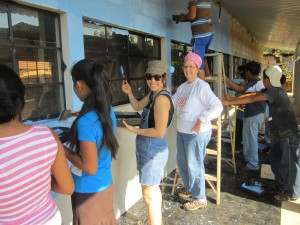 Donors working with the village community to paint the school.