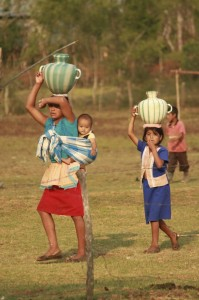 Families carry water from the pond back to their homes to drink.  The large jug holds 4 gallons, or 33 lbs. on the woman's head, plus she carries the weight of her baby.